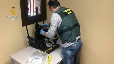 Uno de los agentes analiza una de las mascarillas incautadas. | GUARDIA CIVIL